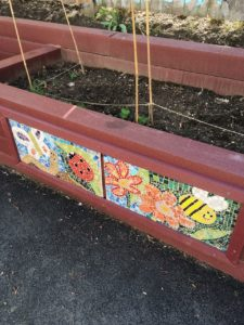 Garden bed mosaics by after school students at the Kennedy School